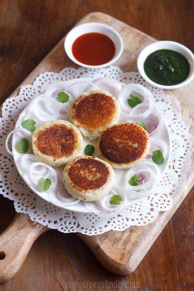 galettes de paneer servies sur une assiette blanche avec des oignons tranchés avec du chutney en accompagnement
