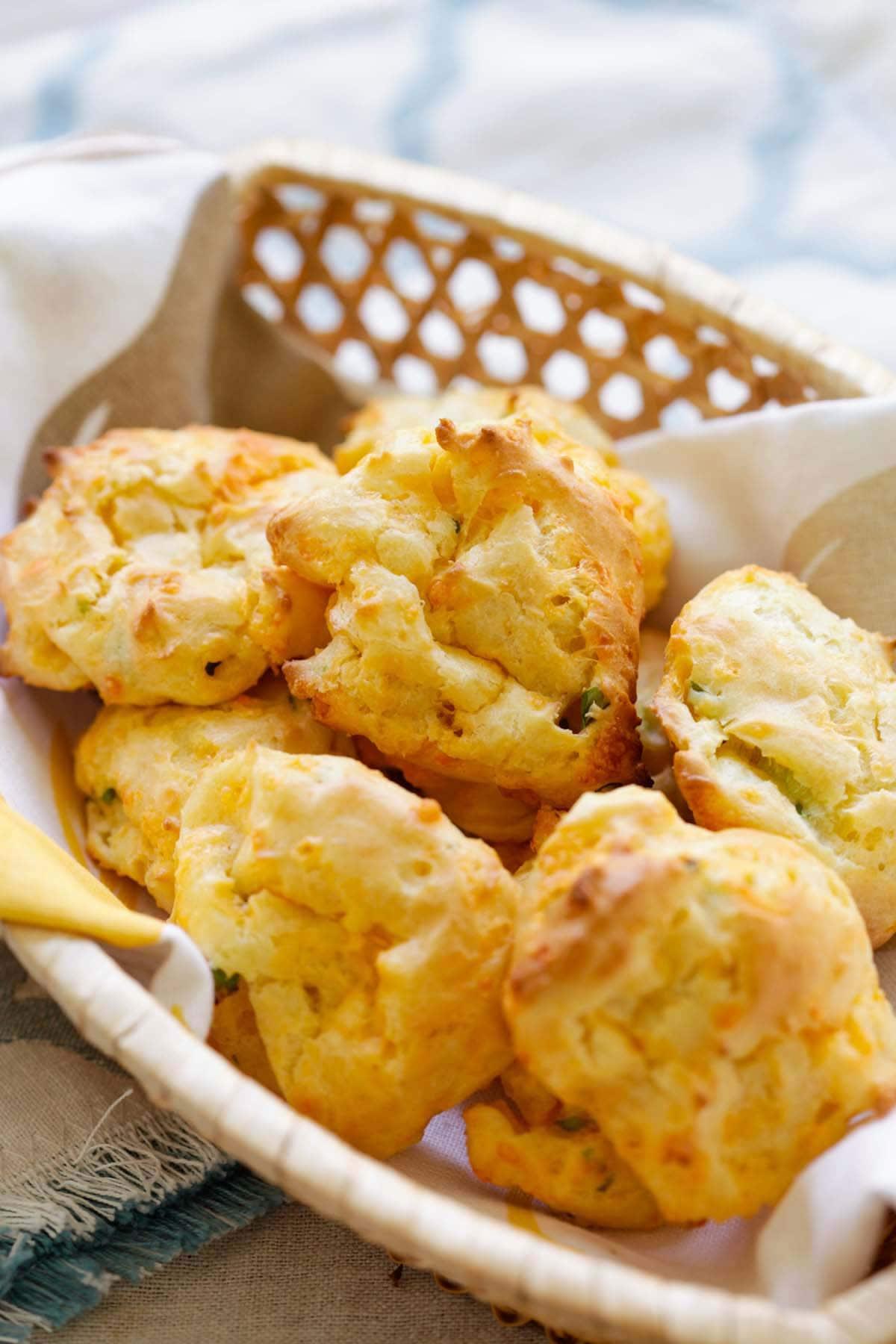 Pâte feuilletée française maison facile et délicieuse à base de fromage cheddar et d'oignons verts hachés servie dans un panier.