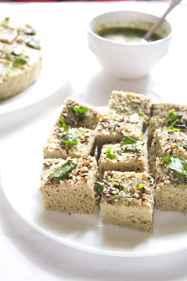 carrés de moong dal dhokla dans une assiette blanche