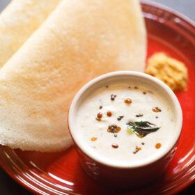 un petit bol blanc de chutney de noix de coco sur une plaque rouge avec deux dosa