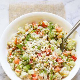 salade de légumes garnie de feta émiettée et de persil avec une cuillère dans un bol blanc