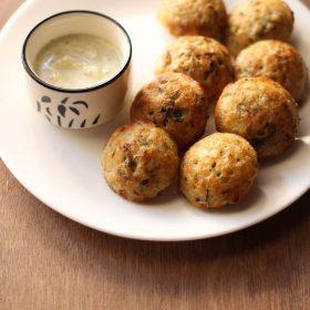 recette de paniyaram servie dans une assiette blanche avec chutney de noix de coco dans un bol